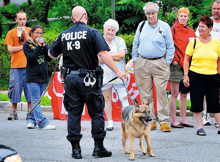Hagerstown City Police K-9 officer T.A. Bartles and his German shepherd, Queen, give a demonstration to those gathered Sunday on Reynolds Avenue in Hagerstown during the Neighborhoods 1st Reynolds Avenue block party and yard sale. (By Joe Crocetta/Staff Photographer)